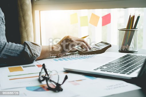 istock Close up of businessman or accountant hand holding pen working on calculator to calculate business data, accountancy document and laptop computer at office, business concept 950688726
