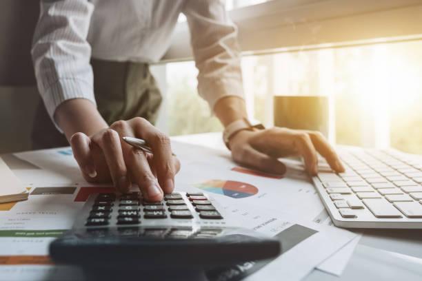 Nahaufnahme von Geschäftsmann oder Buchhalter Hand mit Stift arbeiten am Rechner zur Berechnung von Geschäftsdaten, Rechnungswesen Dokument und Laptop-Computer im Büro, Business-Konzept – Foto