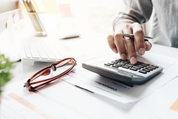 Close up of businessman or accountant hand holding pencil working on calculator to calculate financial data report, accountancy document and laptop computer at office, business concept Close up of businessman or accountant hand holding pencil working on calculator to calculate financial data report, accountancy document and laptop computer at office, business concept calculator stock pictures, royalty-free photos & images