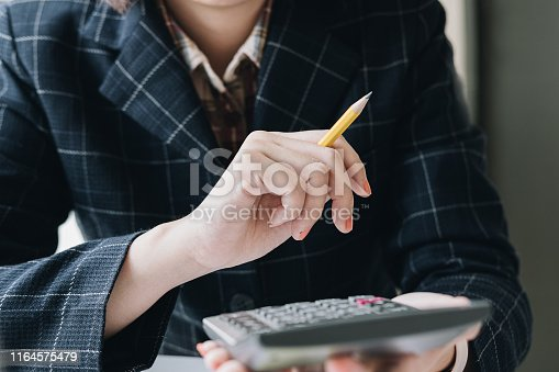 897852992istockphoto Close up of businessman or accountant hand holding pencil working on calculator to calculate financial data report, accountancy document and laptop computer at office, business concept 1164575479