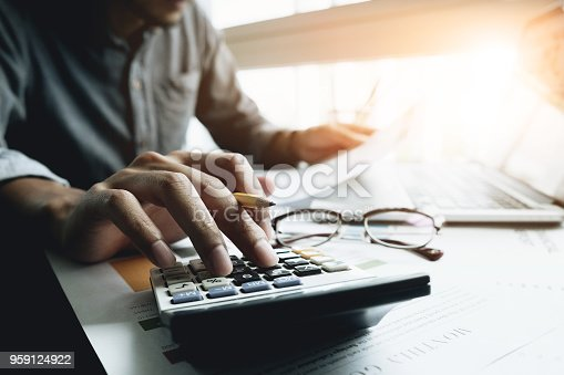 897852992istockphoto Close up of businessman or accountant hand holding pencil working on calculator to calculate financial data report, accountancy document and laptop computer at office, business concept 959124922