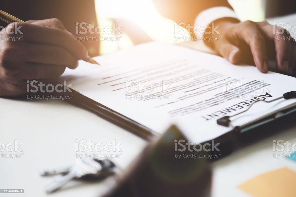 Close up of Businessman pointing and signing agreement contract for buying house. Bank manager and real estate concept. stock photo