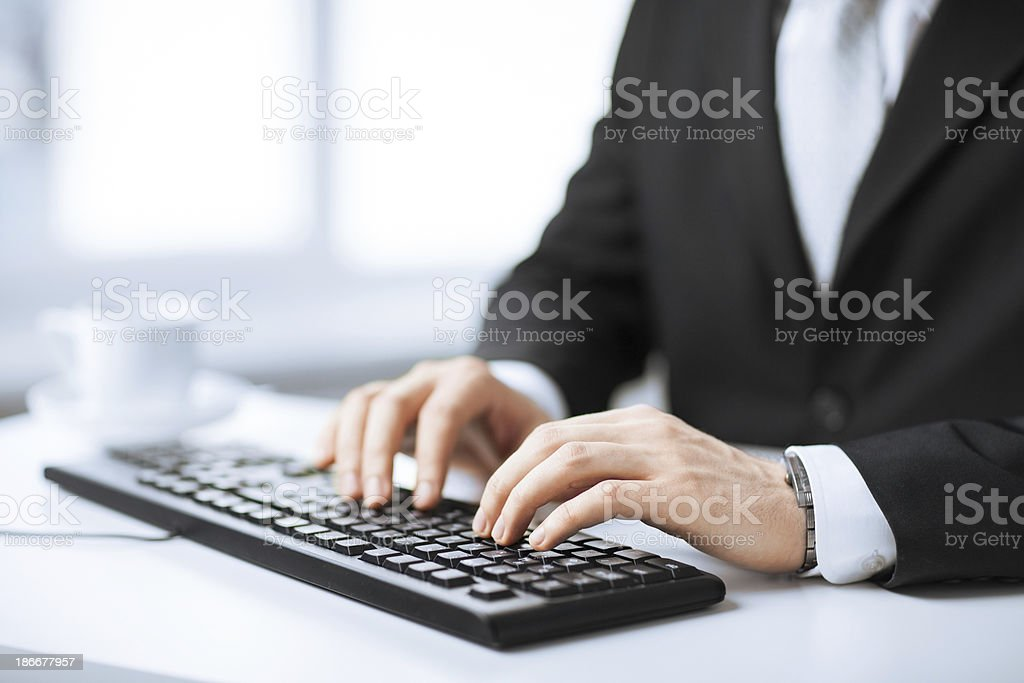Close up of businessman typing on a keyboard stock photo