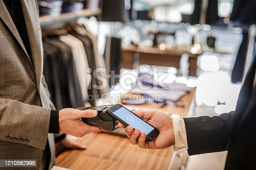 istock Close Up Of Businessman Using Smartphone To Pay For Shopping 1210582995
