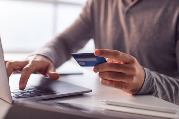 Close Up Of Businessman Working Late On Laptop At Desk Making Online Payment With Credit Card stock photo