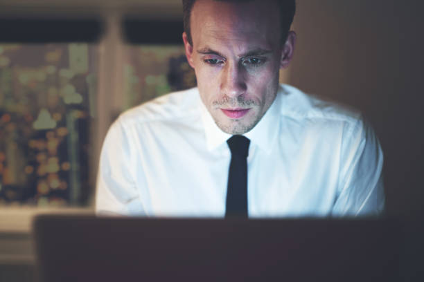 Close up of businessman working overtime on computer stock photo
