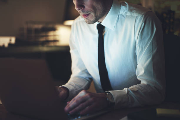 Close up of businessman working overtime stock photo