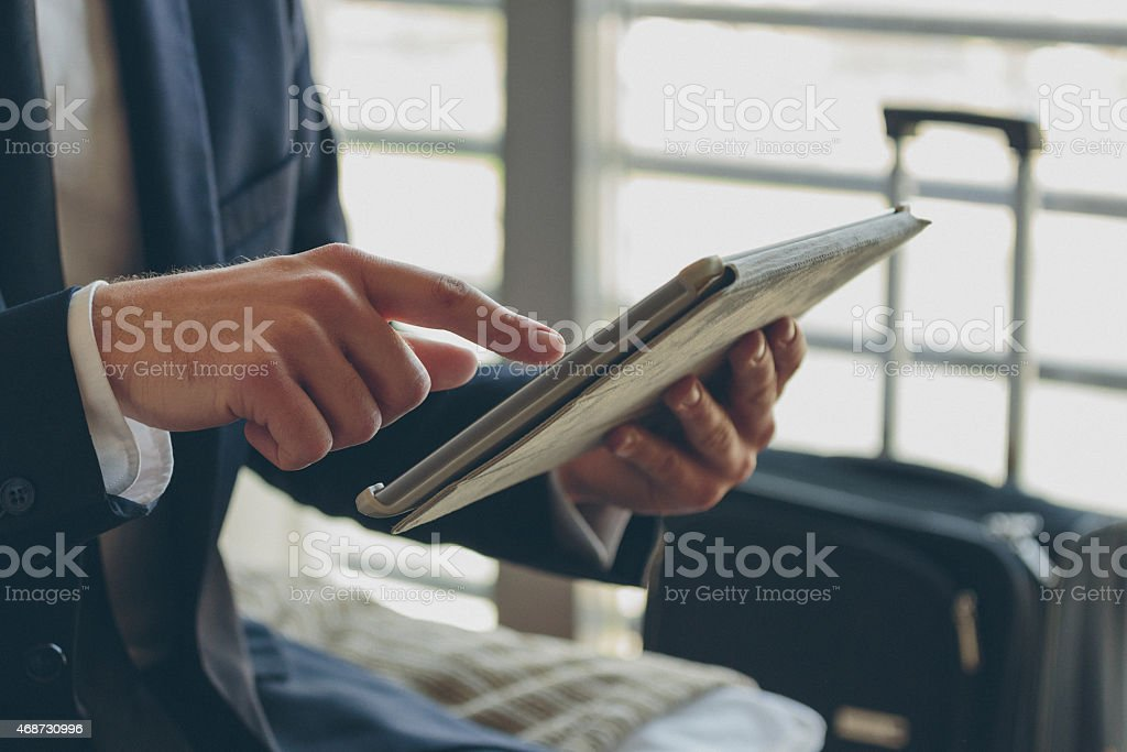 Close up of businessman's hands and digital tablet Businessman wearing suit sitting on bed in hotel room and using a digital tablet. Close up of hands. Unrecognizable person. 2015 Stock Photo