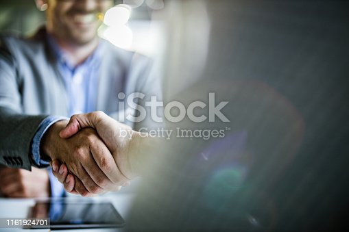 Close up of unrecognizable businessmen shaking hands on a meeting in the office. Copy space.