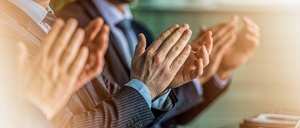Close up of businessmen in suits clapping - foto de acervo