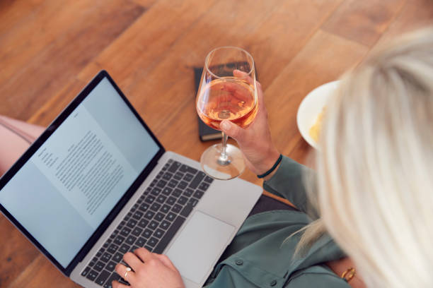 Close Up Of Businesswoman At End Of Day With Wine In Loungewear And Suit On Laptop Working At Home stock photo
