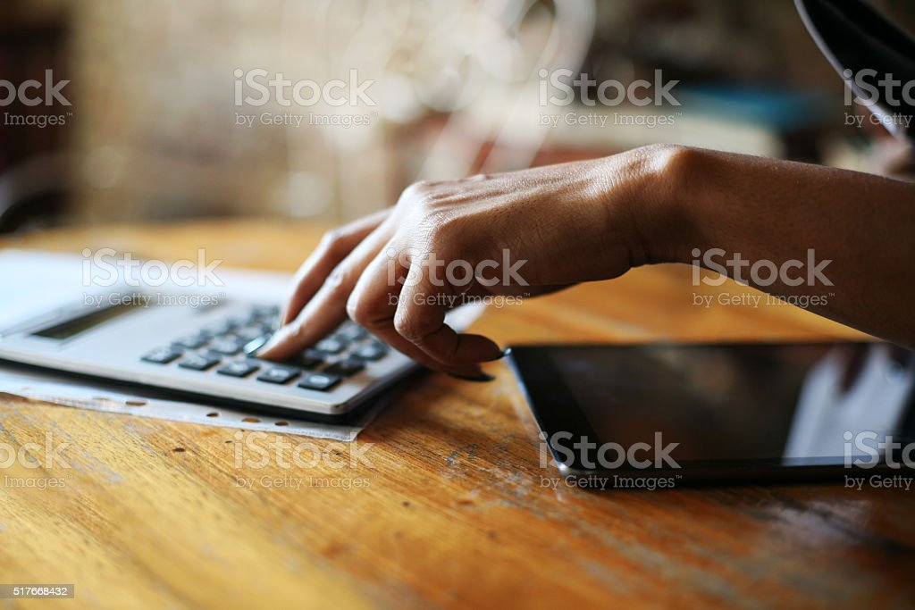 Close up of businesswoman hands using calculator. stock photo