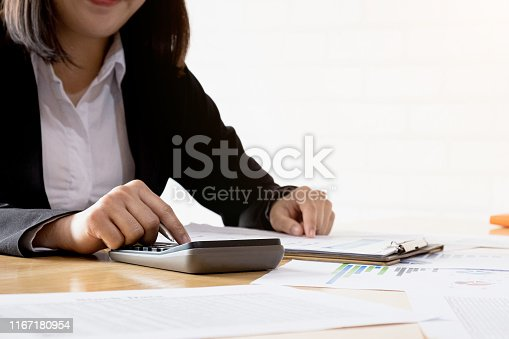 897852992istockphoto Close up of businesswoman or accountant hand holding pen working on calculator to calculate business data, accountancy document and laptop computer at office, business concept 1167180954