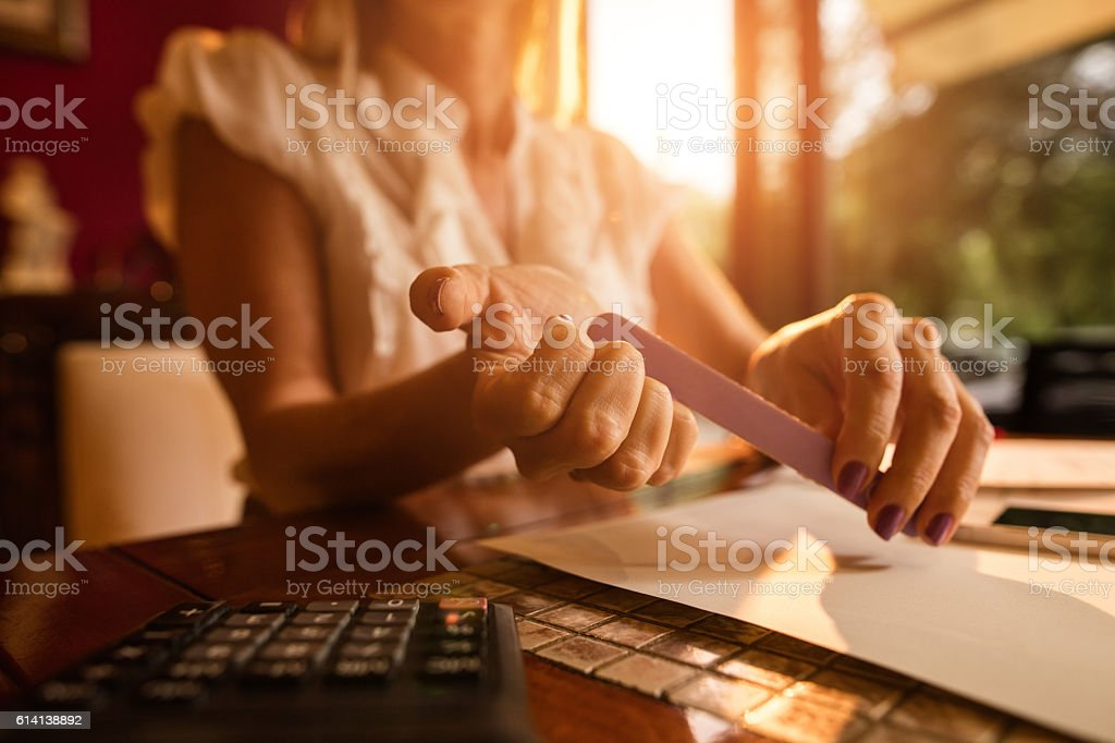 Close Up Of Businesswoman Polishing Nails With Nail File Stock Photo
