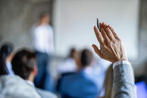 Close up of unrecognizable businesswoman raising her hand to ask the question on a seminar in board room.