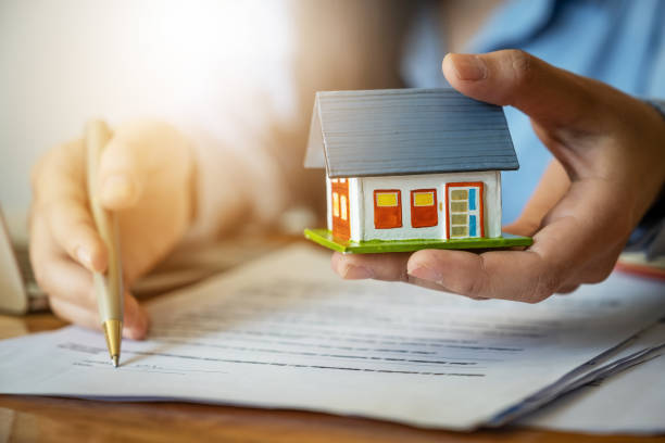 close up of businesswoman with house model and pointing agreement contract. real estate agent concept. - real estate law stock photos and pictures