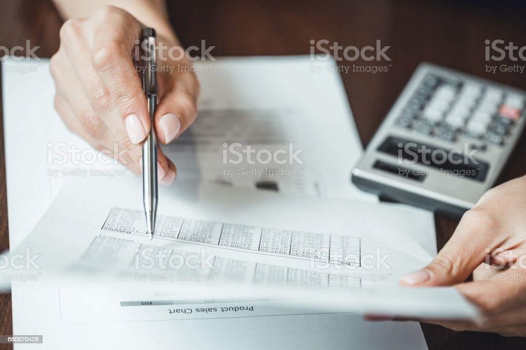 Close up of businesswomans hand with pen doing some financial calculations stock photo