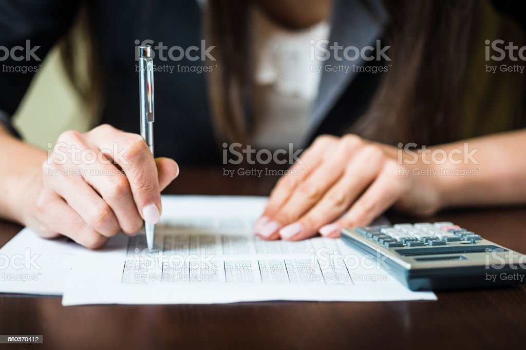 Close up of businesswomans hands with pen doing some financial calculations. Shallow DOF, focus on pen stock photo