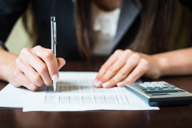 Cerca de las manos businesswomans con pluma hacer cálculos financieros. DOF bajo, foco en la pluma - foto de stock