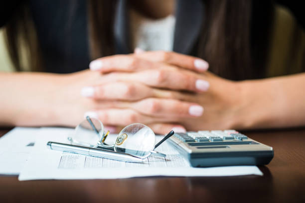 close up of businesswomans hands with pen, glasses, and calculator doing some financial calculations - wages stock photos and pictures