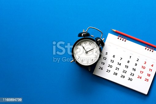 istock close up of calendar, alarm clock, pencil on the blue table background, planning for business meeting or travel planning concept 1165894739