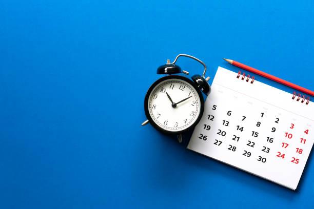 zbliżenie kalendarza, budzik, ołówek na niebieskim tle stołu, planowanie spotkania biznesowego lub koncepcji planowania podróży - czas zdjęcia i obrazy z banku zdjęć