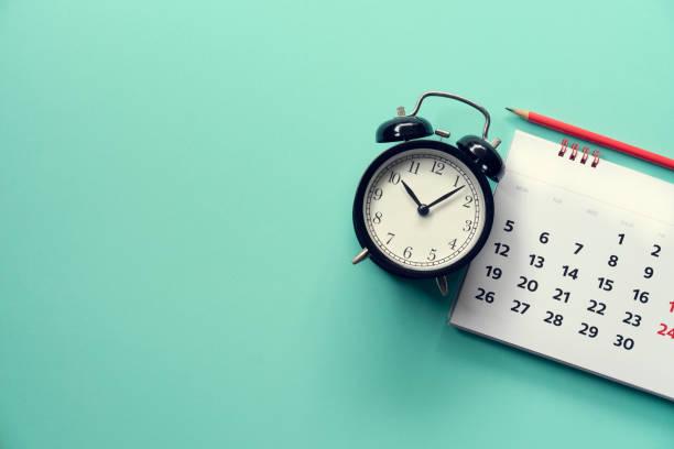 zbliżenie kalendarza i budzik na zielonym tle, planowanie spotkania biznesowego lub koncepcji planowania podróży - czas zdjęcia i obrazy z banku zdjęć