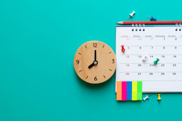 close up of calendar and clock on green background, planning for business meeting or travel planning concept stock photo