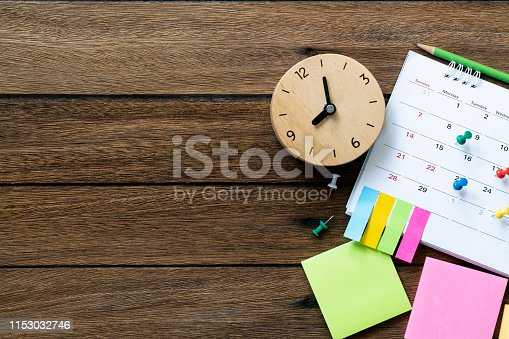 close up of calendar and clcok on the table, planning for business meeting or travel planning concept