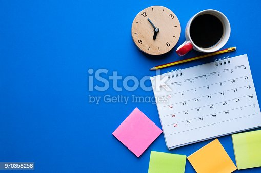 istock close up of calendar, coffee, clock and pencil on the blue table background, planning for business meeting or travel planning concept 970358256