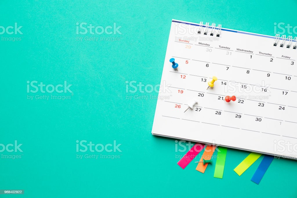 close up of calendar on the table with green background, planning for business meeting or travel planning concept stock photo