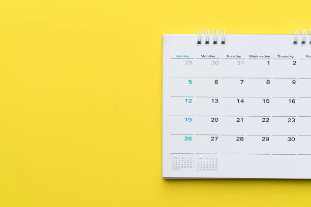 close up of calendar on yellow background, planning for business meeting or travel planning concept - calendar stock photos and pictures