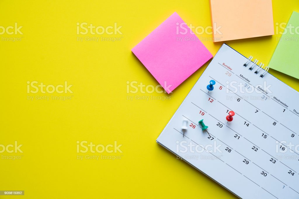 close up of calendar on yellow background, planning for business meeting or travel planning concept stock photo