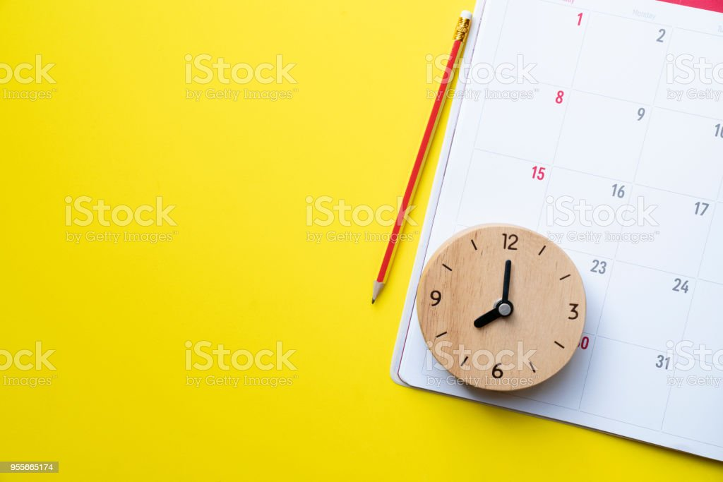 close up of calendar or monthly planner on the yellow background, planning for business meeting or travel planning concept stock photo
