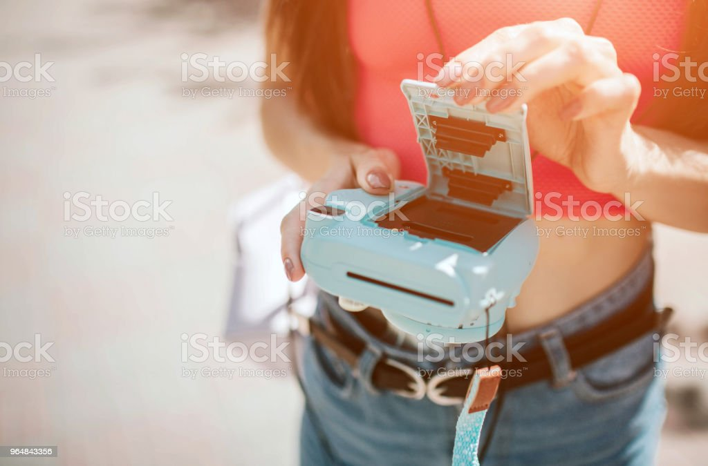Close up of camera with opened back. Girl has done it. She is holding camera in her hands. Also she is holding lid from camera's back royalty-free stock photo