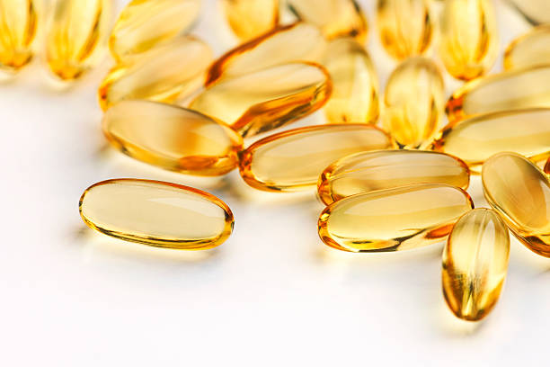 close up of capsules (see below for two other versions) - cod liver oil stock photos and pictures