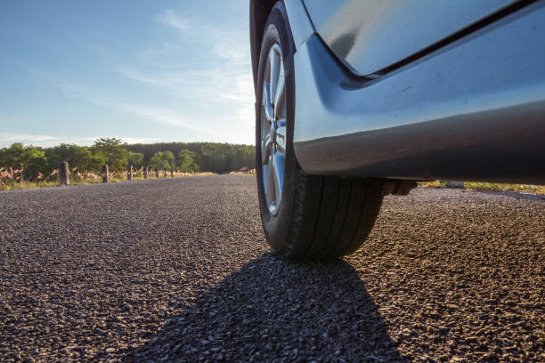 Close up of car wheels on asphalt road, travel concept, aim stock photo