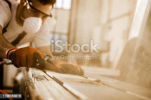 Close up of a male carpenter blowing sawdust from a plank with air pump in a workshop.