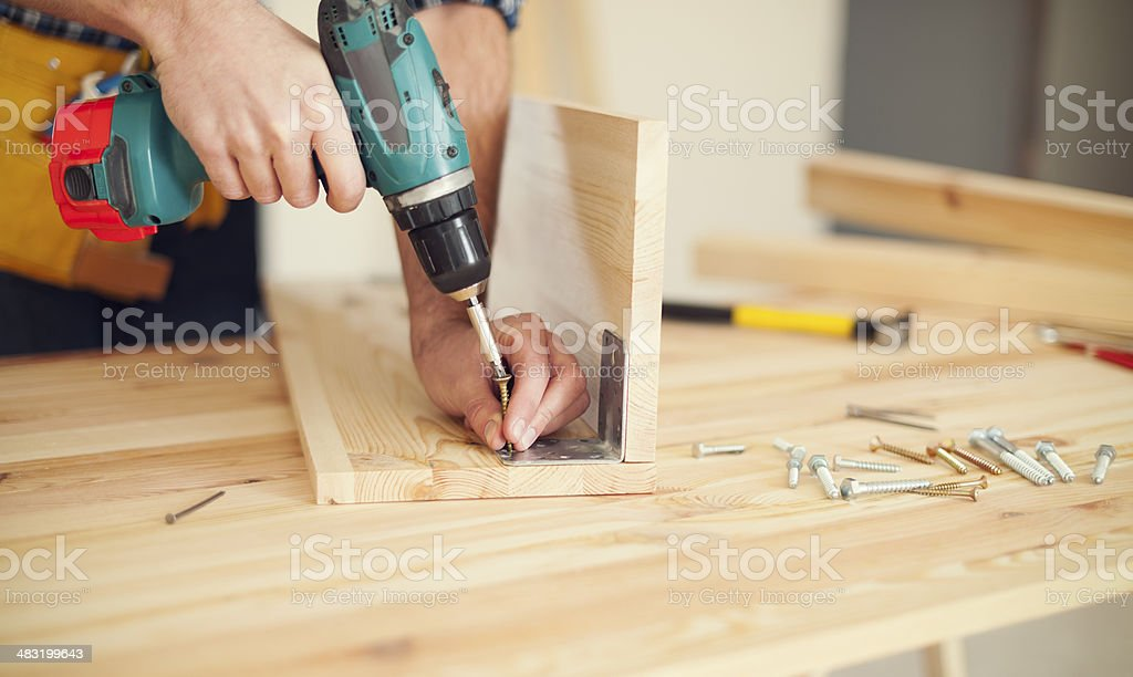 Close up of carpenter working with drill stock photo