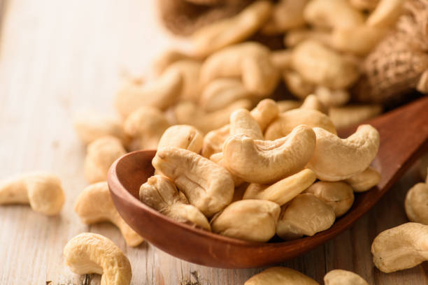 close up of cashew nuts in wood spoon on wood table - cashew stock photos and pictures