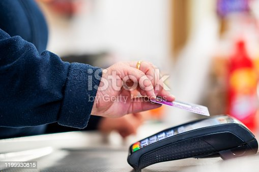 Close up of cashier is using contactless credit card pos terminal to getting the payment