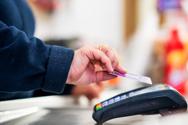 close up of cashier is using contactless credit card pos terminal to getting the payment. - paying with card contactless imagens e fotografias de stock