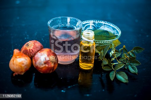 istock Close up of caster oil,onion juice mixture used to make hair stronger and thicker on wooden surface.; 1129352153