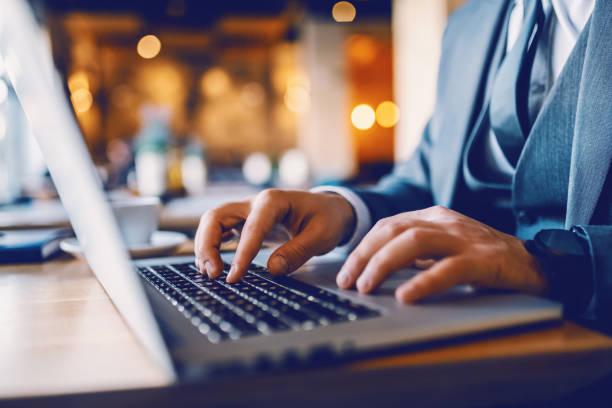 Close up of caucasian businessman in suit sitting in cafe and typing on laptop financial report. hands are on keyboard. stock photo