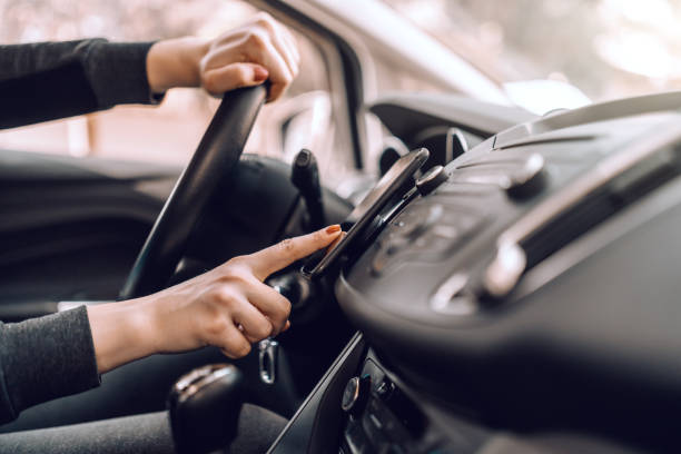 close up of caucasian pregnant woman driving car and turning on gps on smart phone. other hand on steering wheel. - acessório imagens e fotografias de stock