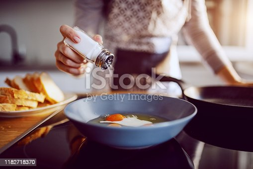 istock Close up of caucasian woman adding salt in sunny side up eggs while standing in kitchen next to stove. 1182718370
