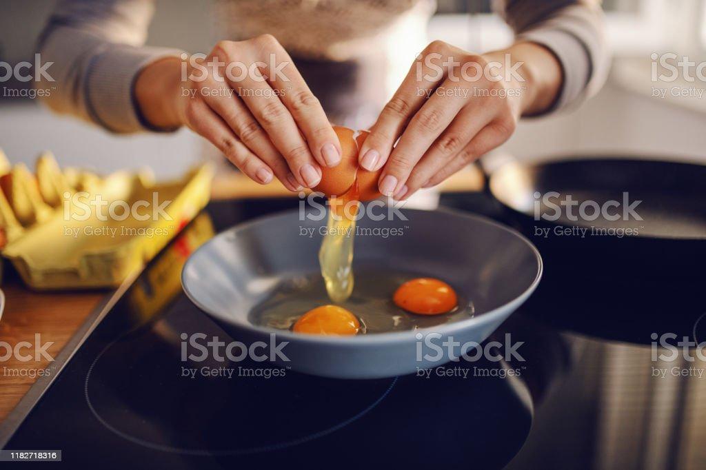 Close-up van blanke vrouw breken ei en het maken van zonnige kant omhoog eieren. Binnenlandse keuken interieur. Ontbijt bereiding. - Royalty-free Binnenopname Stockfoto