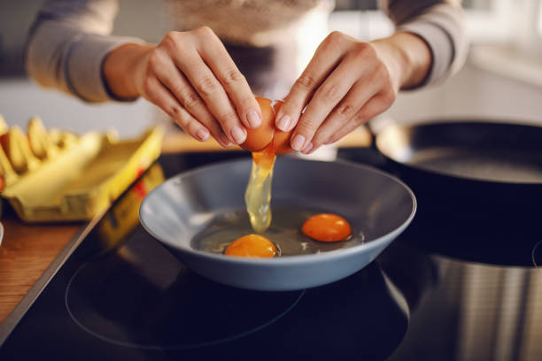 Close up of caucasian woman breaking egg and making sunny side up eggs. Domestic kitchen interior. Breakfast preparation. Close up of caucasian woman breaking egg and making sunny side up eggs. Domestic kitchen interior. Breakfast preparation. animal egg stock pictures, royalty-free photos & images