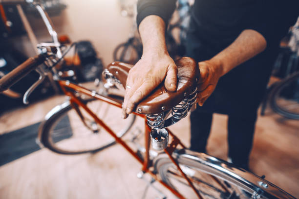 Close up of Caucasian worker putting saddle on bicycle. Bike workshop interior. Close up of Caucasian worker putting saddle on bicycle. Bike workshop interior. bicycle shop stock pictures, royalty-free photos & images