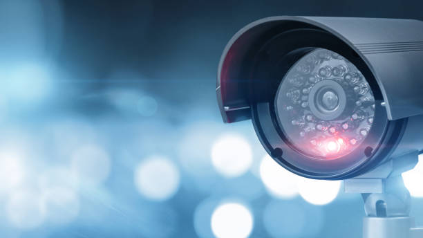 Close up of CCTV camera over defocused urban background Close up of CCTV camera over defocused background with copy space security stock pictures, royalty-free photos & images